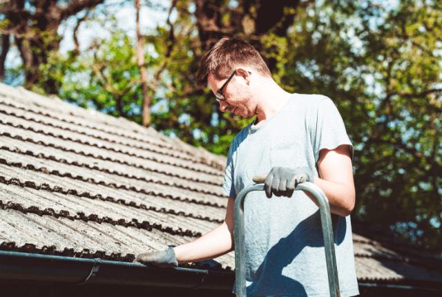 איש מנקה את הגג לפני החורף
